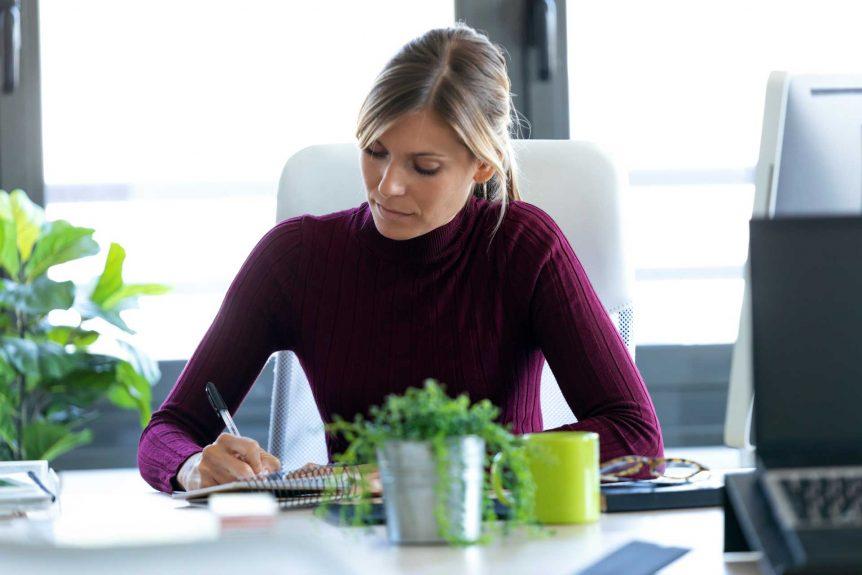 Cómo usar un sencillo ejercicio de escritura inspirado en un principio de Toyota para tener más dinero, perder peso y ser más feliz concentrated young business woman taking notes VXLJCYY 862x575